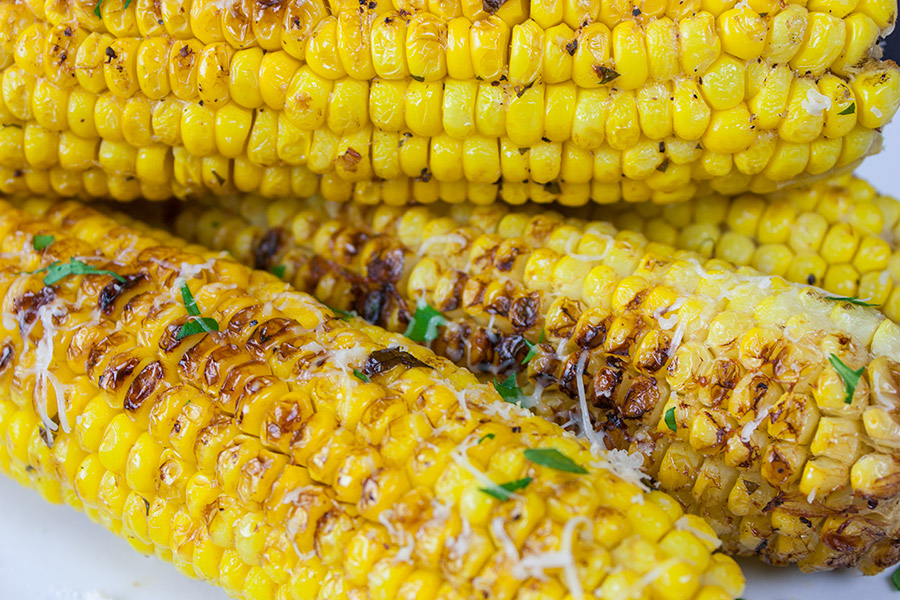 Grilled Parmesan Corn On The Cob on a white platter garnished with parsley and parmesan cheese