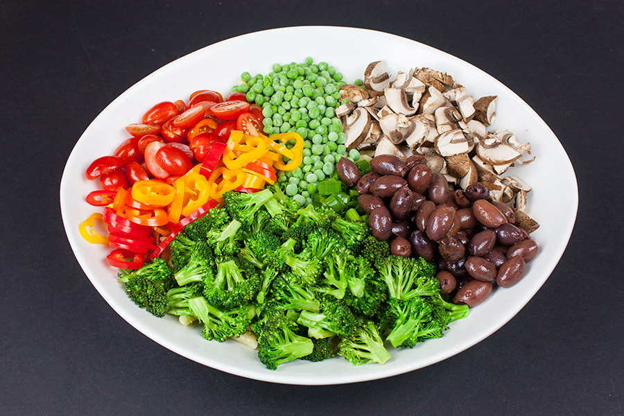 tomatoes, peas, mushrooms, broccoli, and olives for Lemon Veggie Pasta Salad in a large white serving bowl