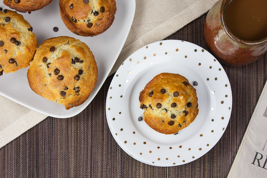 baked Bakery Style Chocolate Chip Muffins on white plates