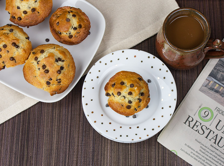 Chocolate Chip Muffins on large white platter one on white plate with gold dots brown background