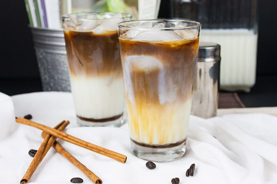Iced Cinnamon Macchiato in two clear glasses cinnamon sticks and espresso beans scattered around
