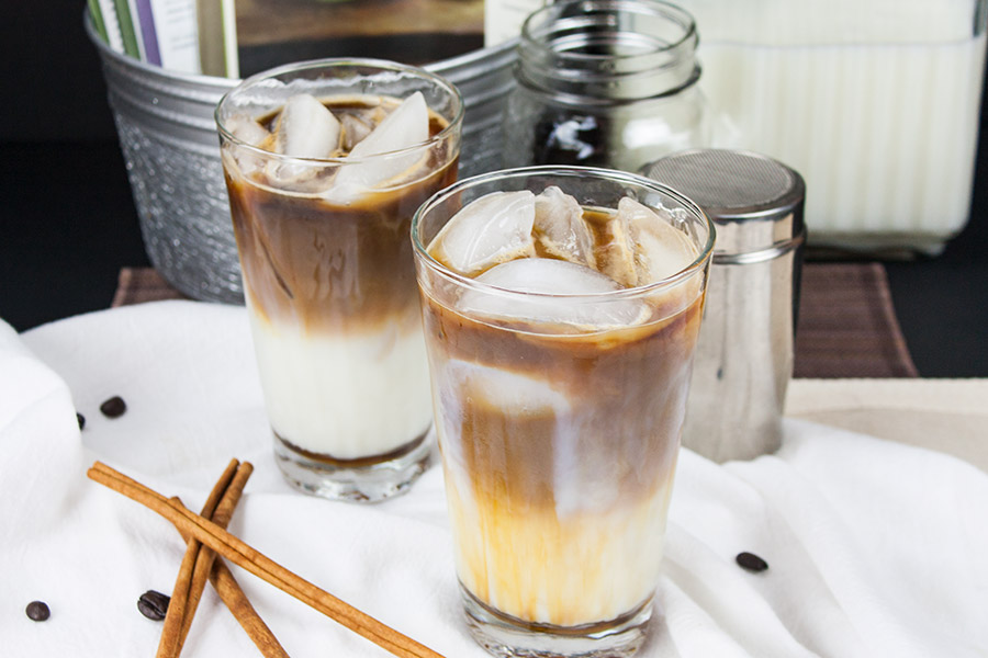 two Iced Cinnamon Macchiatos in clear glasses on white cloth cinnamon sticks and espresso beans tossed around