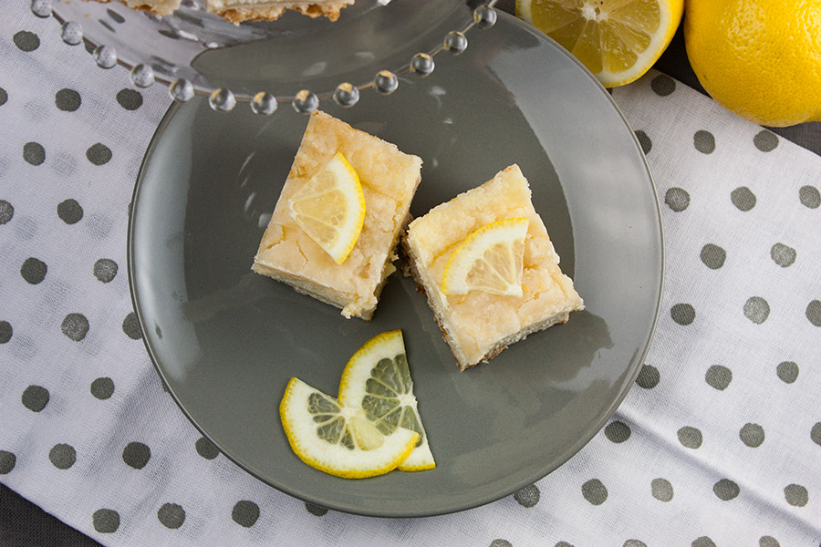 two Lemon Cheesecake Shortbread Bars garnished with lemon slices on gray plate over white with gray dots cloth