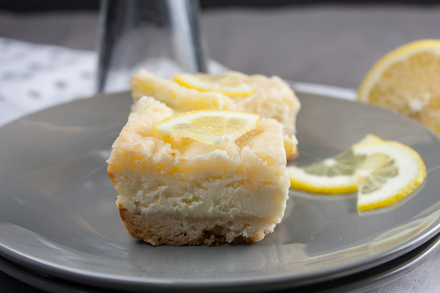 Lemon Cheesecake Shortbread Bar slices on gray plate with lemon slices