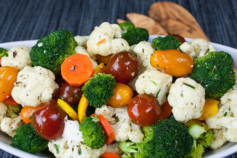 marinated fresh vegetable salad in a white oval bowl wooden spoons
