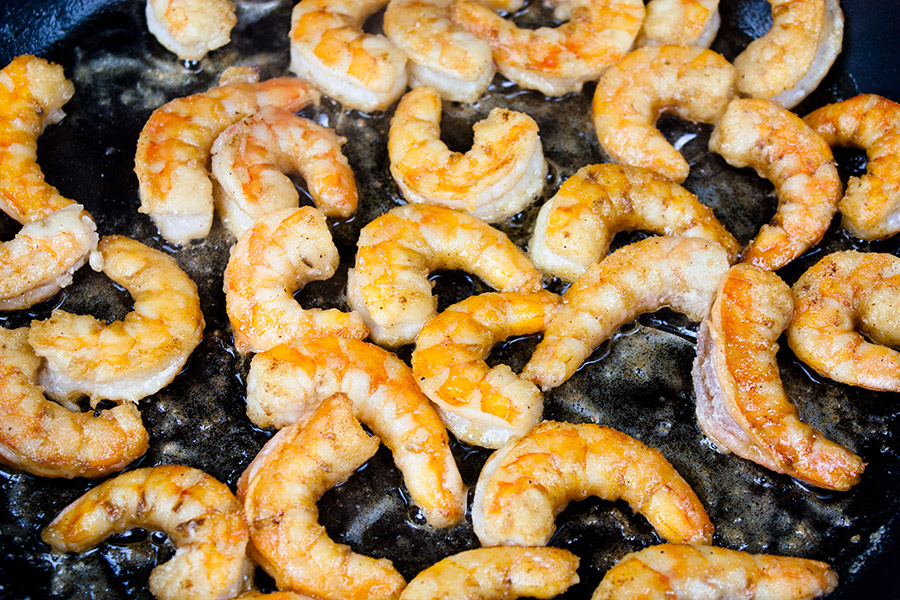 shrimp sauteing in cast iron skillet