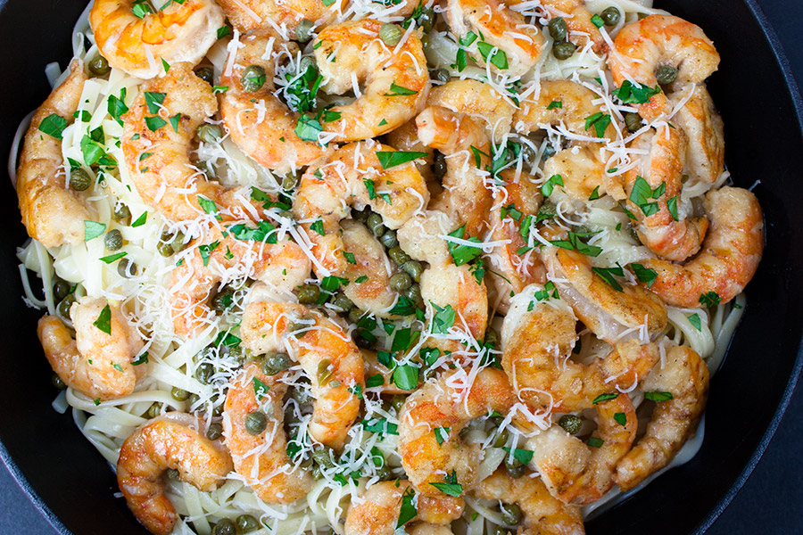 shrimp piccata garnished with capers parsley and parmesan cheese