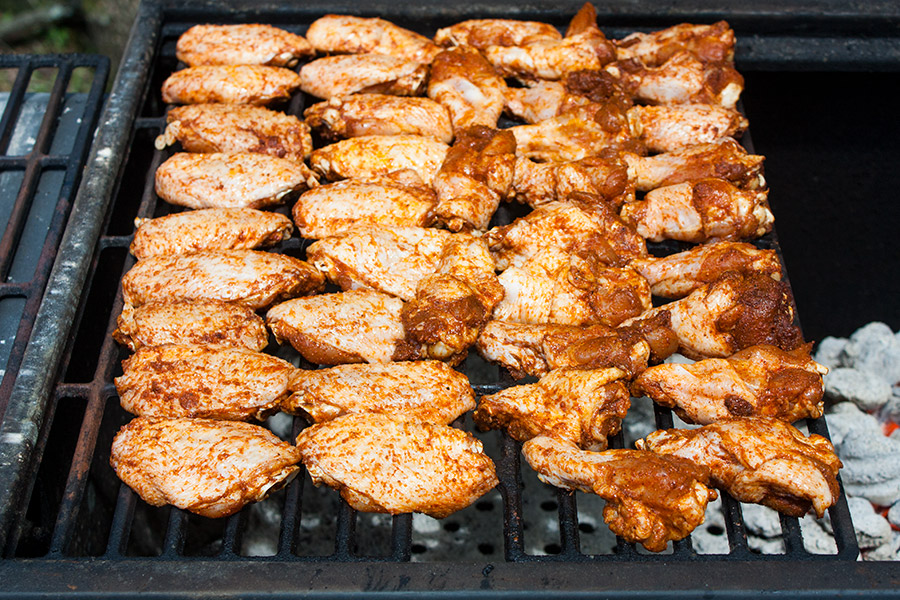 raw chicken wings covered in dry rub on the grill