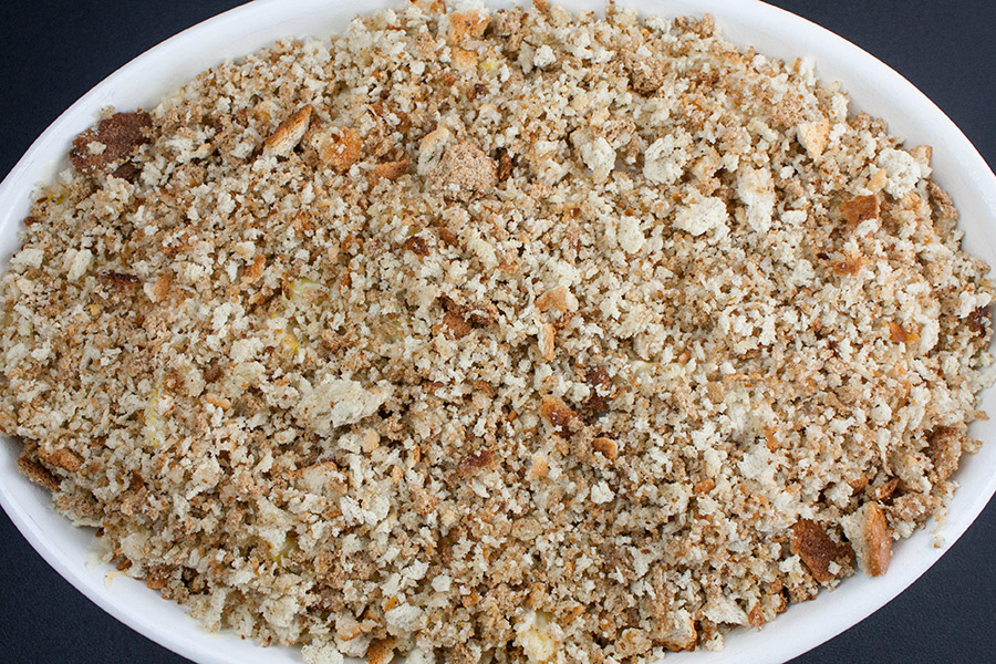 Squash Casserole topped with bread crumb mixture in white casserole