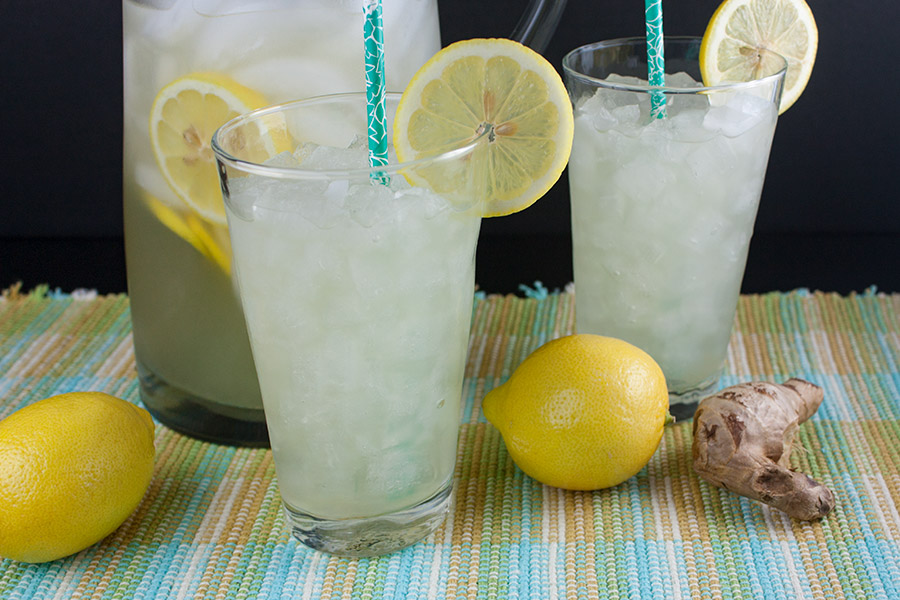 Honey Ginger Lemonade in glass pitcher and two tall glasses garnished with lemon slices
