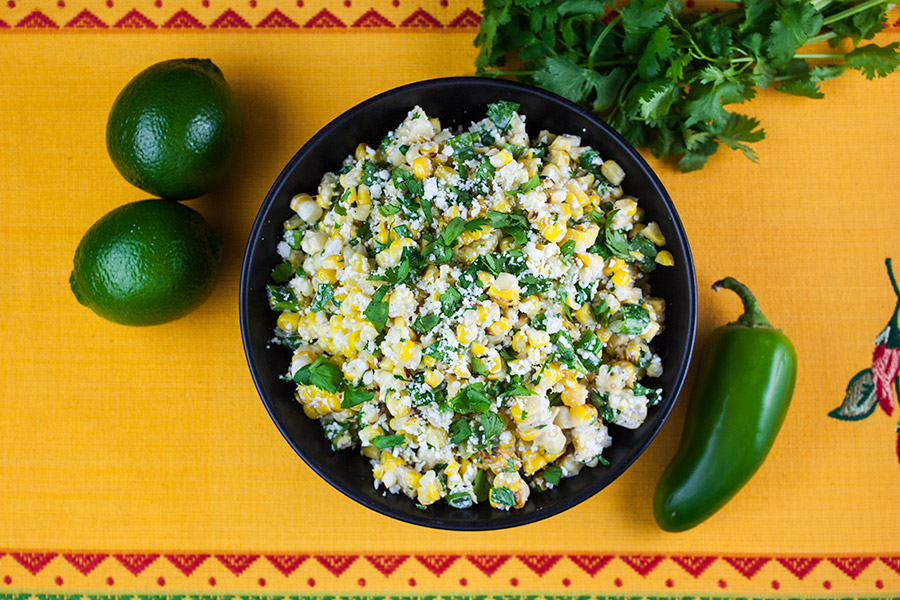 Grilled Mexican Street Corn Salad in black bowl on yellow place mat