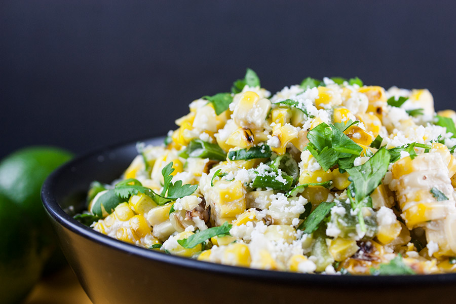 close up of Grilled Mexican Street Corn Salad in black bowl