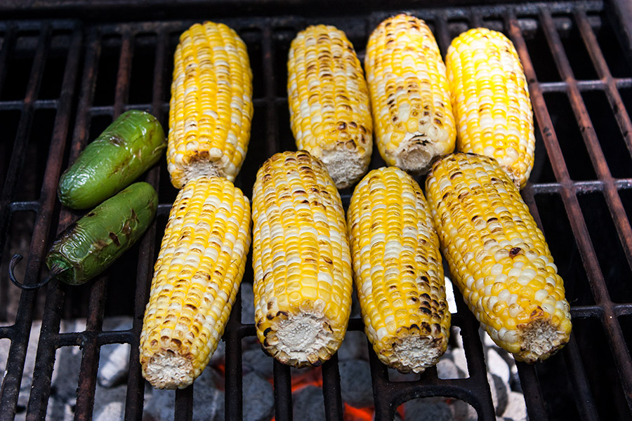 corn cobs and jalapenos on grill grate