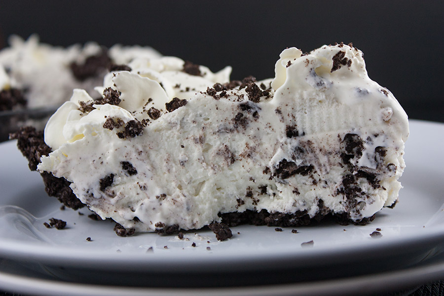 slice of No Bake Cookies and Cream Pie on white plate cookie crumbs scattered