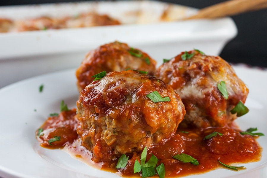 three Baked Parmesan Meatballs on white plate garnished with sauce and chopped parsley