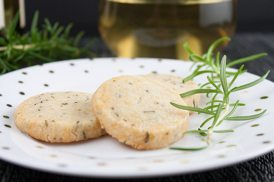 Savory Parmesan Rosemary Shortbread on white plate rosemary garnish wine glass in background