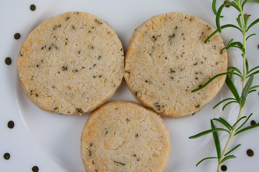 Parmesan Rosemary Shortbread on white with gold dots fresh rosemary sprig