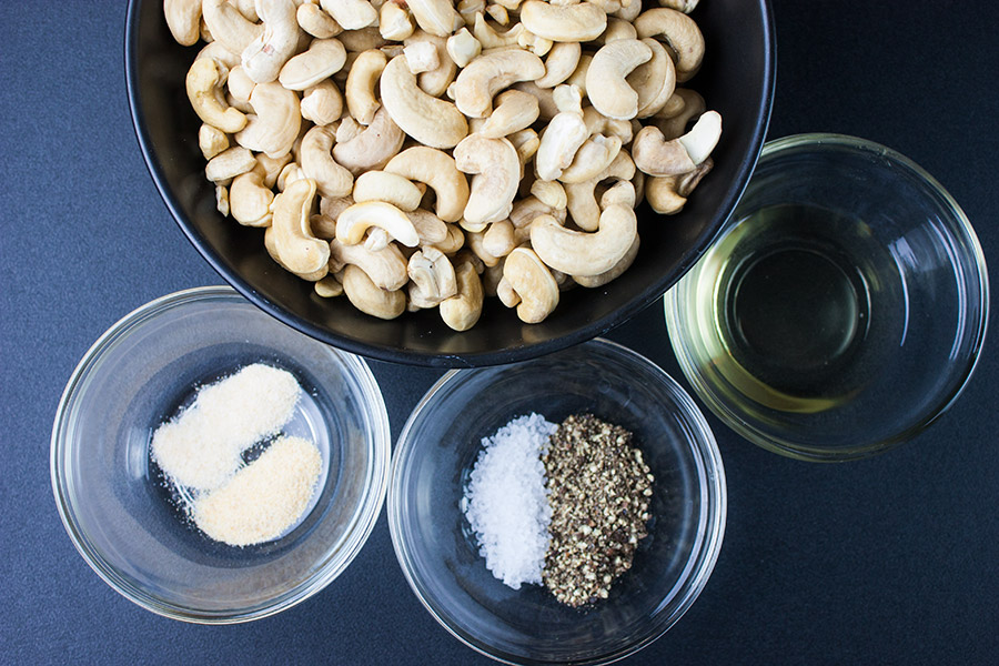 Salt and Pepper Cashews - raw cashews in black bowl small glass ramekins with spices and oil