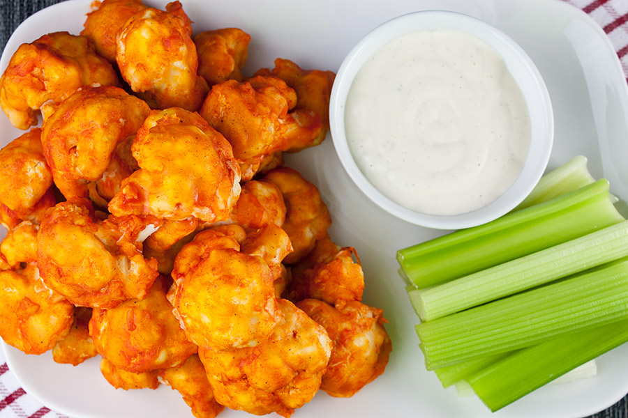 cauliflower on white platter with celery and ranch dip