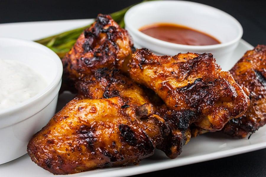 wings on white plate sauce in white ramekin