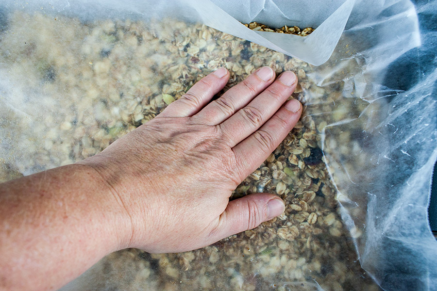hand pressing the granola in the pan using wax paper