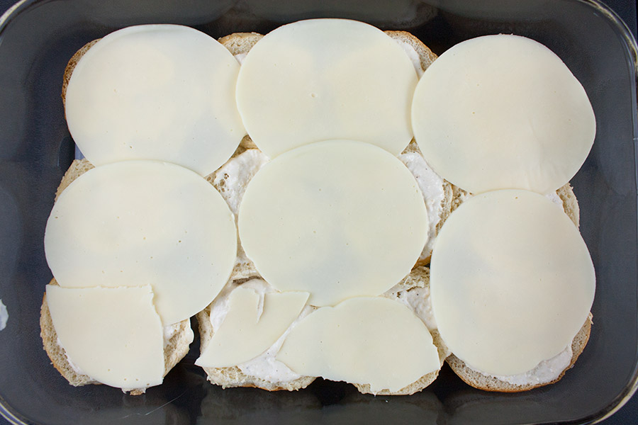 bottom of buns topped with horseradish sauce and cheese
