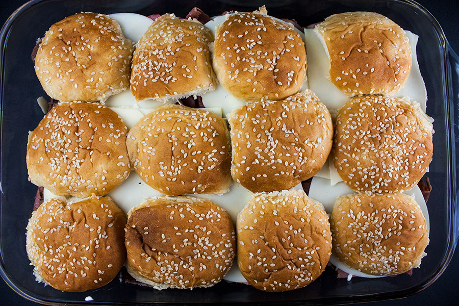 top buns placed on top of cheese in baking dish