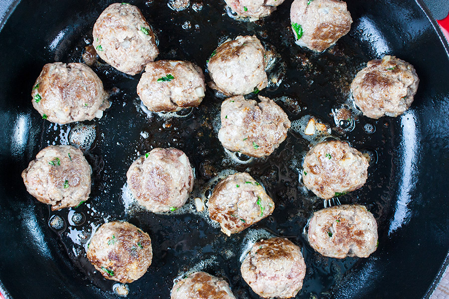 swedish meatballs browning in cast iron skillet
