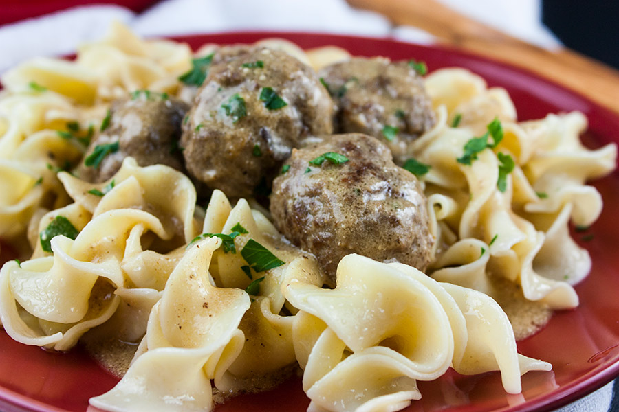 Swedish meatballs over egg noodles on red plate garnished with chopped parsley