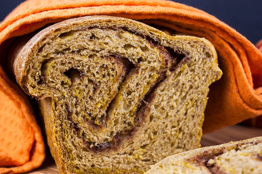 baked bread sliced wrapped in an orange towel