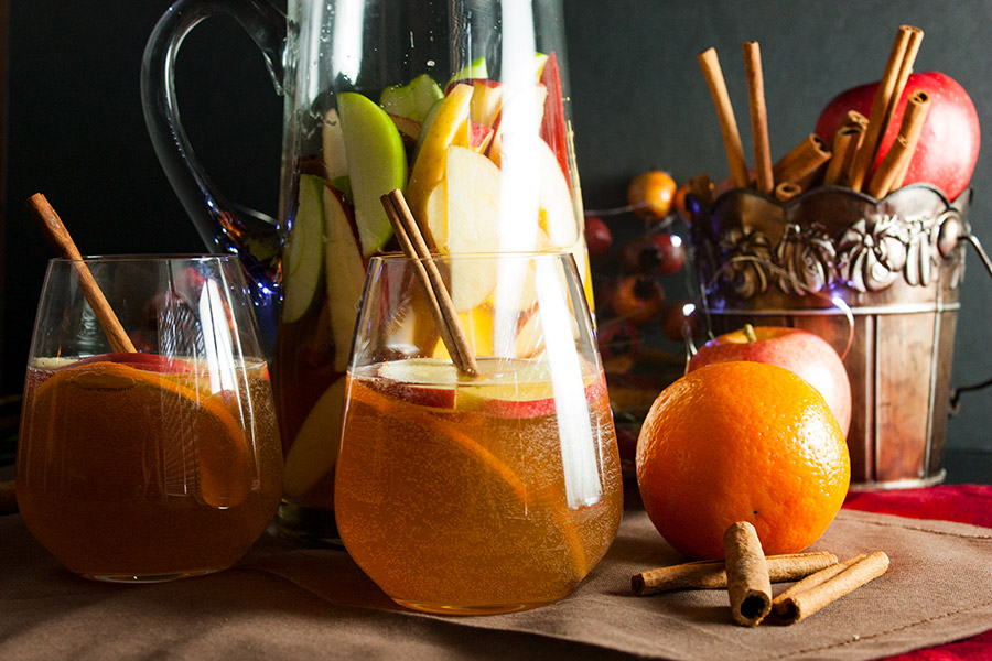 Cider Ginger Beer Sangria in 2 no stem wine glasses garnished with cinnamon sticks