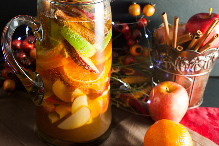 Cider Ginger Beer Sangria in a clear glass pitcher with slices of apples oranges cinnamon sticks