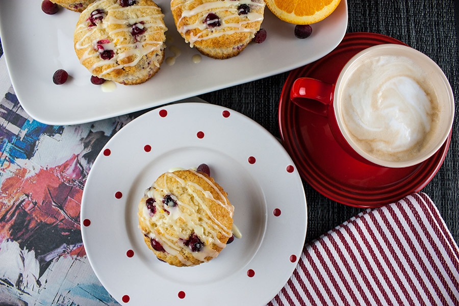 baked Cranberry Orange Muffins on a white plate with red dots and a red cappuccino cup and saucer