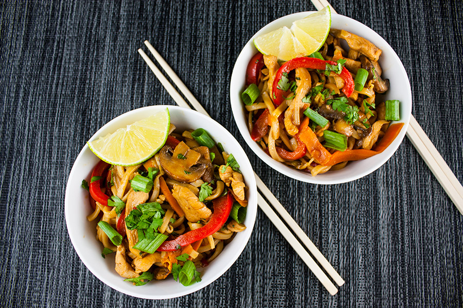 Spicy Thai Chicken Noodle Bowl - dished in two white serving bowls wedge of lime chopsticks