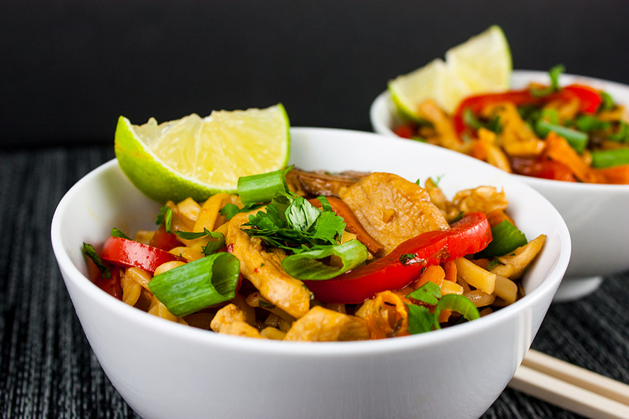 Spicy Thai Chicken Noodle Bowl - close up cooked dish in two white serving bowls wedge of lime chopsticks