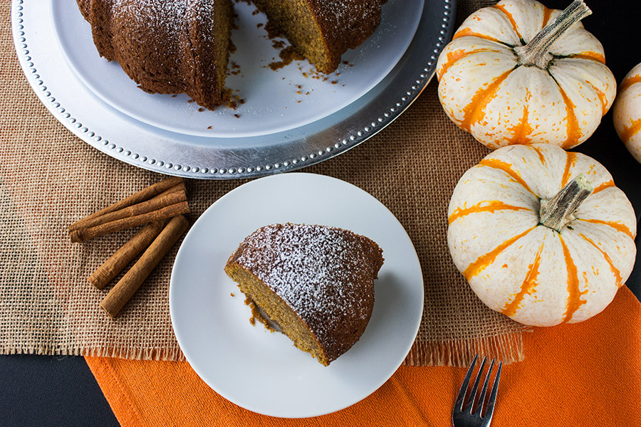 cake on white cake plate with a slice on white plate and small white and orange pumpkins