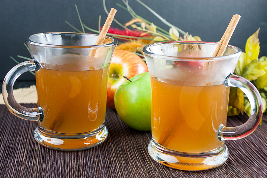 apple cider in two clear mugs garnished with cinnamon sticks