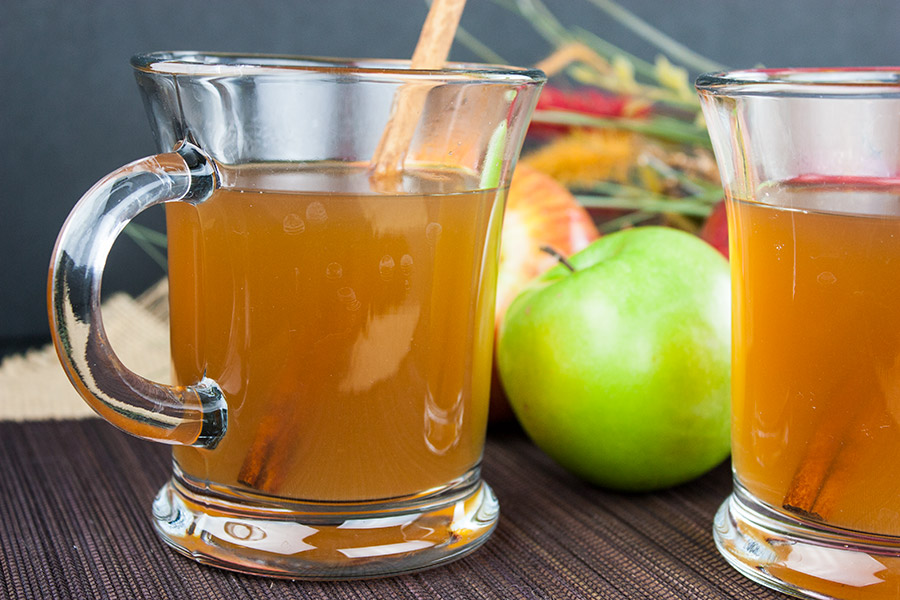 Slow Cooker Apple Cider in clear glass mug with cinnamon stick garnish