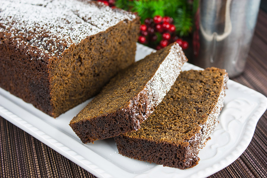 Gingerbread Loaf dusted with powdered sugar and sliced on a white platter