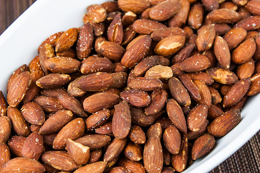 roasted salted almonds in an oval white serving dish