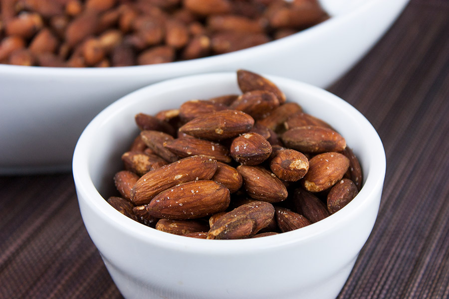 roasted salted almonds in a single serving white ramekin with large serving dish in background