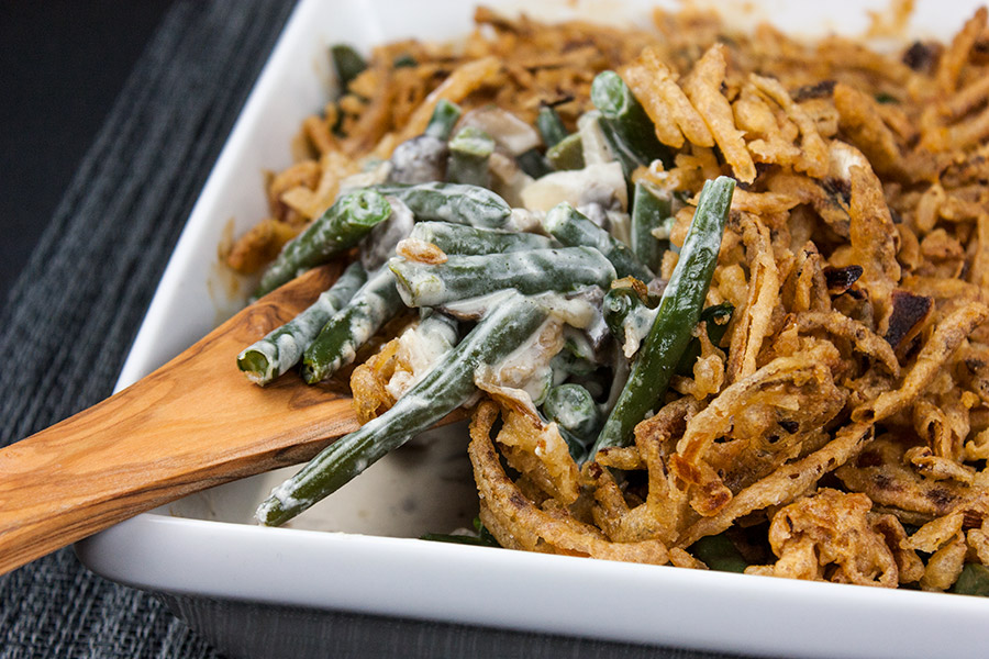 Green Bean Casserole in a white baking pan with wooden spoon
