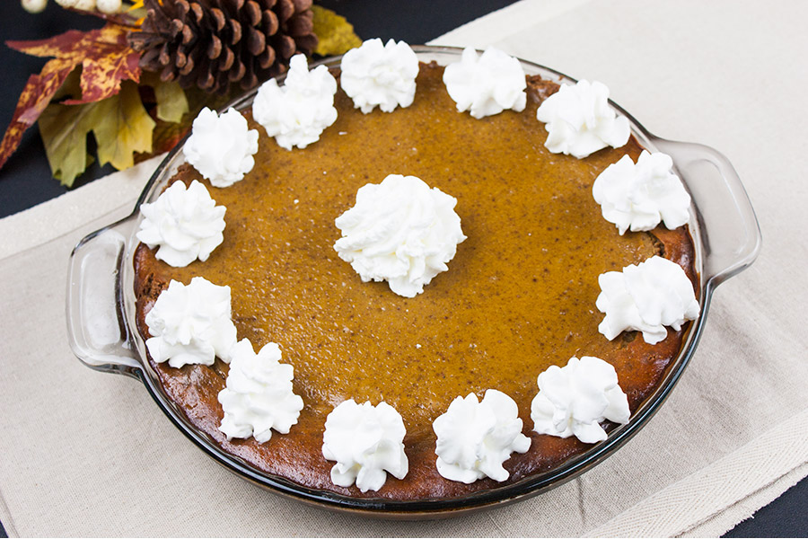 gingersnap crust pumpkin pie garnished with whipped cream topping in a glass pie dish