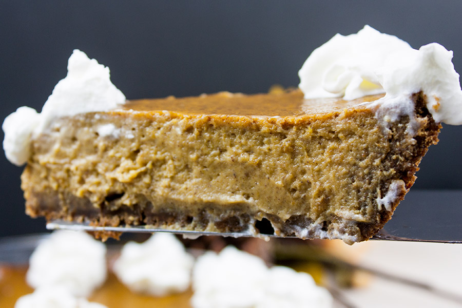 slice of gingersnap crust pumpkin pie with whipped cream garnish