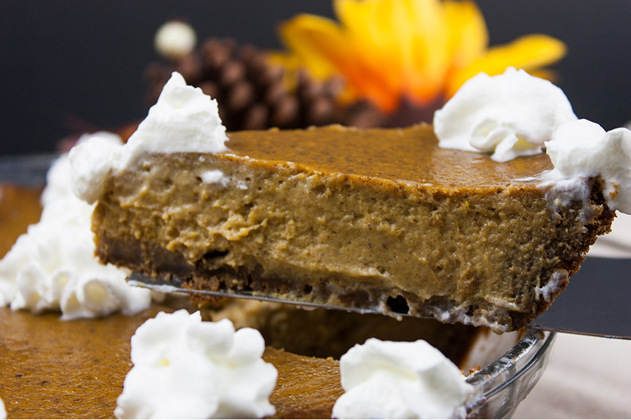 serving slice of gingersnap crust pumpkin pie lifted above the whole pie