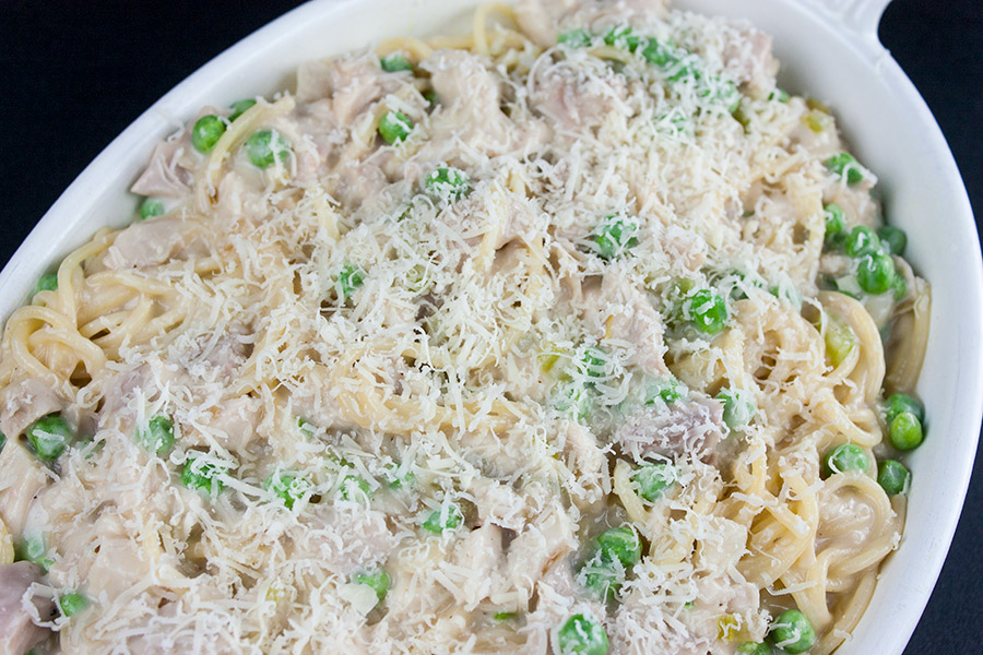 unbaked Turkey Tetrazzini in a white casserole dish topped with Parmesan cheese