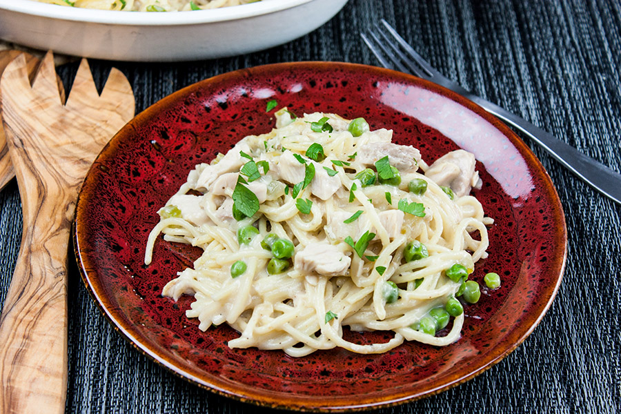 turkey tetrazzini served on a red and black pottery plate