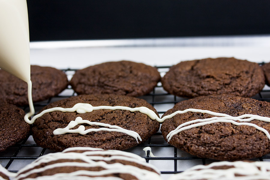 baked cookies on wire rack drizzling the white chocolate over the tops