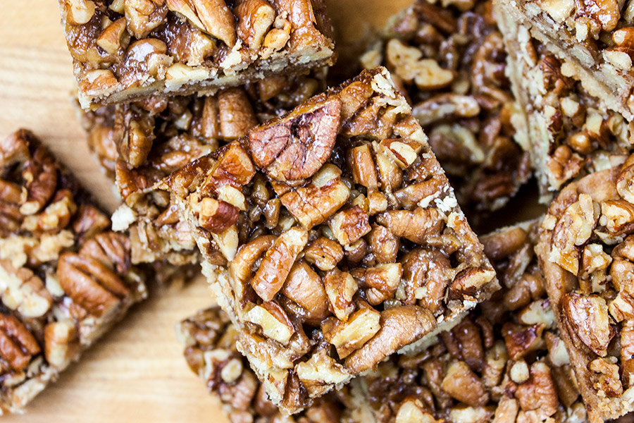 finished pecan pie bars cut into serving size pieces stacked on a wooden cutting board