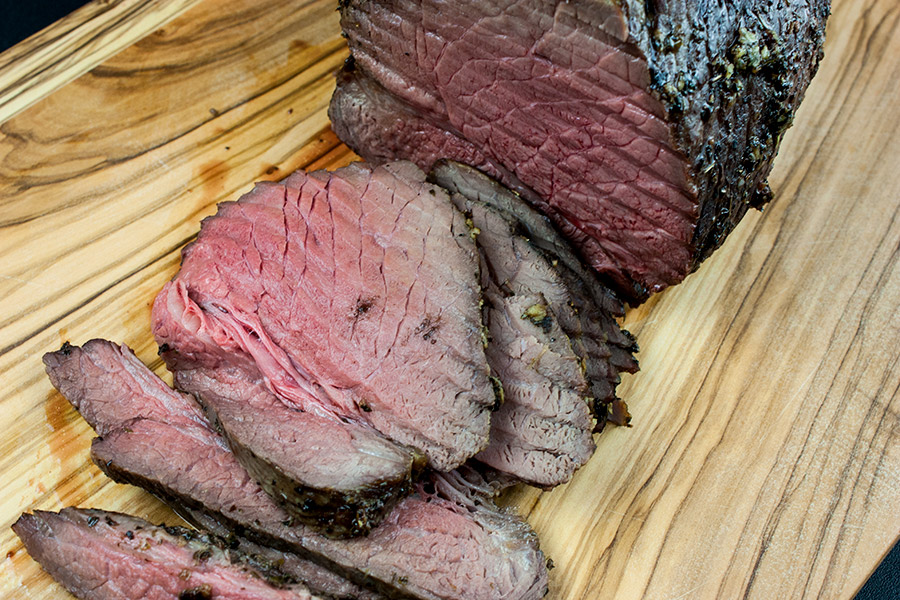 medium-rare roast beef sliced on a wooden cutting board